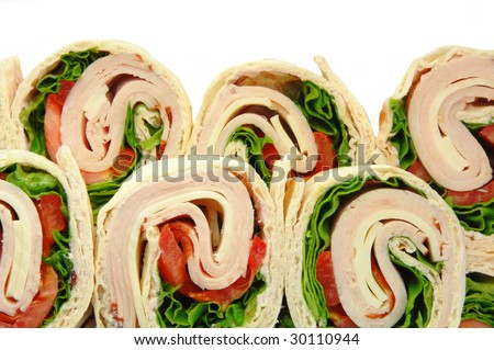 Turkey wrap sandwiches with tomato cheese and lettuce. Viewed from above on a plate. - stock photo
