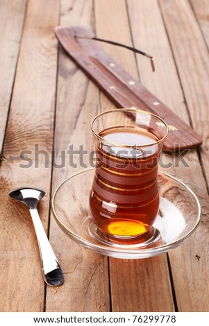 Turkish apple tea in traditional glass and plate on wooden background - stock photo