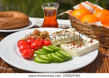 Turkish breakfast with cheese, vegetables, simit, and tea - stock photo