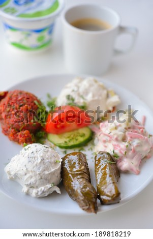 Turkish breakfast with dolma, salads, vegetables, and ayran - stock photo
