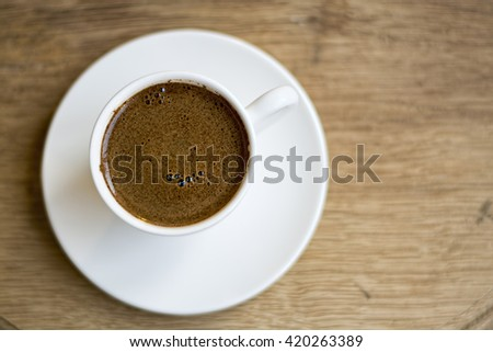 Turkish Coffee in White Porcelain Cup Top View - stock photo