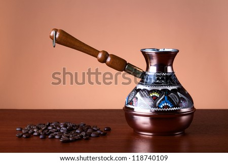 Turkish coffee pot and a handful of roasted coffee beans