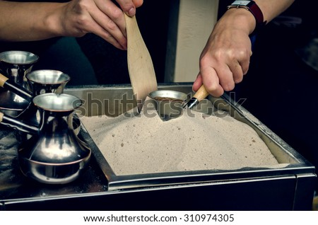 Turkish coffee pots jezve. Drink brewed on the sand - stock photo