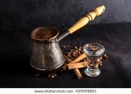 Turkish coffee, with beans and cinnamon on dark background