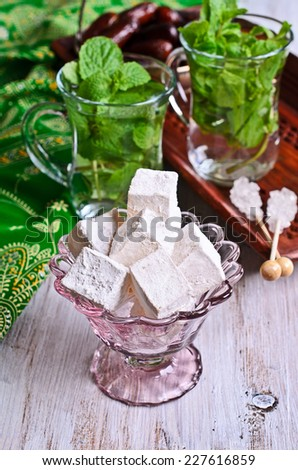 Turkish delight in a glass vase on a background of tea with mint - stock photo