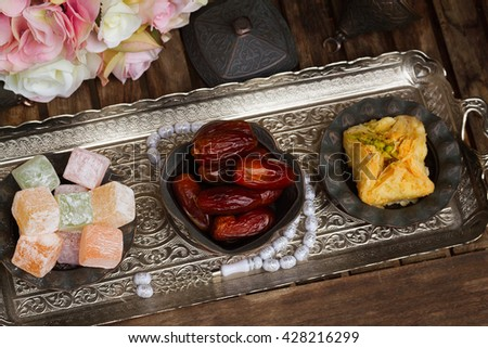 Turkish delights with tasbih on silver oriental tray with flowers - stock photo