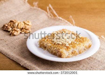 Turkish dessert kadayif with walnut on burlap texture - stock photo