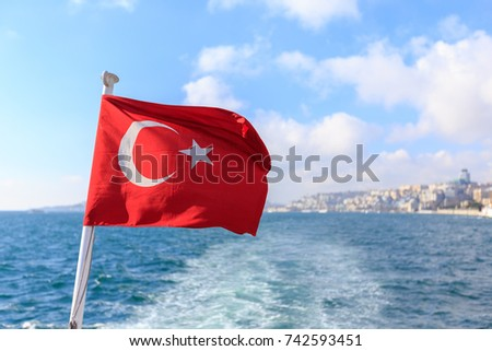 Turkish flag waving against blue sky over the Bosphorus strait in Istanbul, Turkey.
