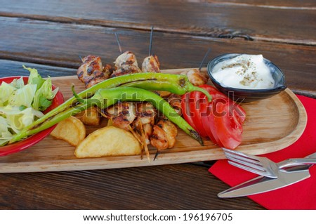 Turkish food (chicken ,pepper grill with fries potatoes and salad) on wooden plate outdoor served