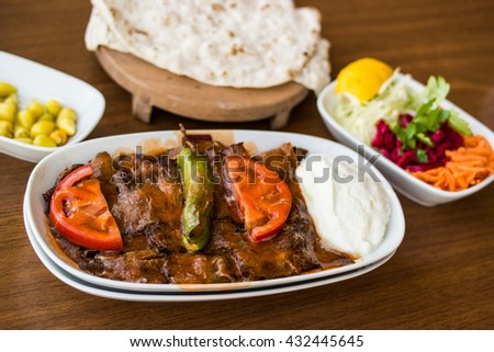 turkish iskender kebab with garniture on a wooden surface at restaurant