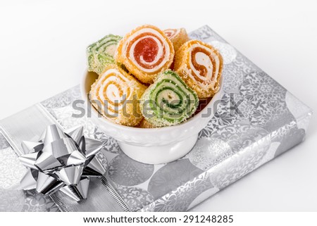 Turkish lokum rolls in a bowl placed on a silver gift box. festive elements. - stock photo