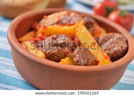 Turkish meatball kofte with potato under tomato sauce. Selective focus - stock photo