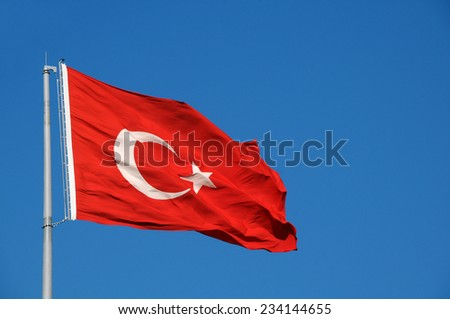 Turkish national flag waves in the breeze against the blue sky background - stock photo