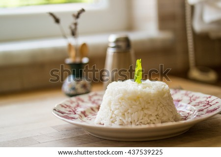 Turkish plain pilaf-rice with salt and black pepper on a wooden surface in the kitchen front view - stock photo
