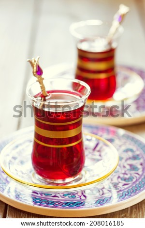 Turkish pomegranate tea in a traditional glasses. Toning in vintage style. Shallow DOF - stock photo