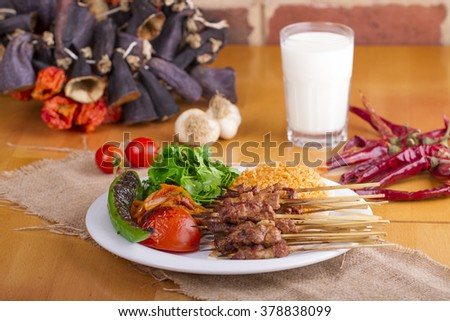 Turkish Sis Kebab in a plate on wooden table with garnish and traditional drink ayran - stock photo