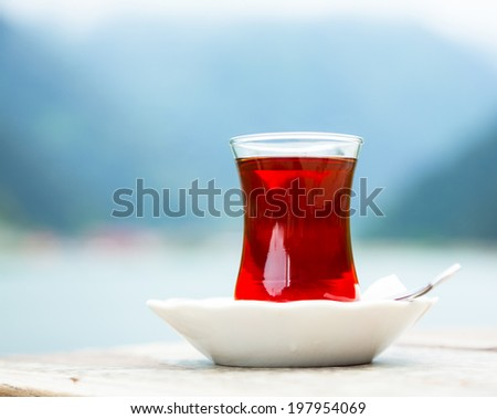 Turkish tea served in traditional glass and plate against mountains - stock photo
