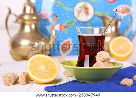 Turkish tea with cane sugar and lemon on a white table - stock photo