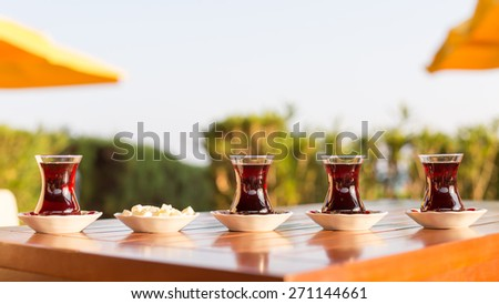 Turkish tea with locum in outdoor cafe. Direct sunset light. Shallow DOF and lightly toned - stock photo