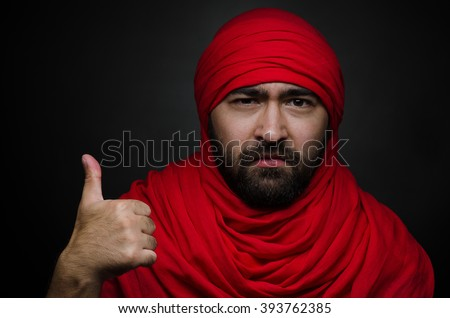 Turkish theme: beautiful Arabic man with a beard in a red scarf showing gestures isolated on black background in studio