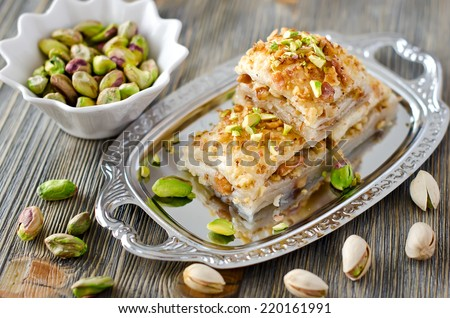turkish traditional dessert with nuts and pistachios wooden background - stock photo