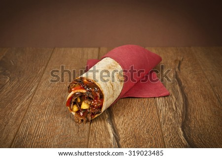 Turkish traditional doner meat chicken with vegetables cheddar cheese wrap on wooden background - stock photo