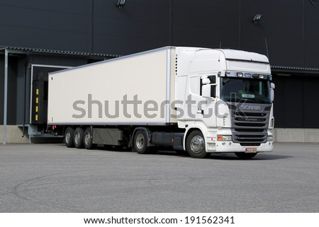TURKU, FINLAND - APRIL 26, 2014: White Scania R440 truck unloading at a warehouse. According to Statistics Finland, 71 million tonnes of goods were transported by lorries in the Q4 of 2013.