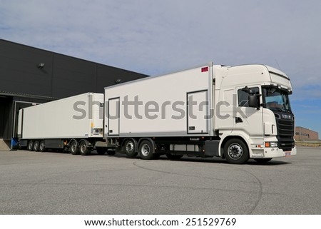 TURKU, FINLAND - APRIL 26, 2014: White Scania R560 truck unloading at a warehouse. According to Statistics Finland, the volume of goods transported by lorries grew by 11% in the Q3 of 2014. - stock photo