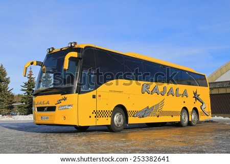 TURKU, FINLAND - FEBRUARY 15, 2015: Yellow Volvo coach bus at bus parking. Volvo Buses launches unique digital customer game to initiate dialogue with customers.  - stock photo