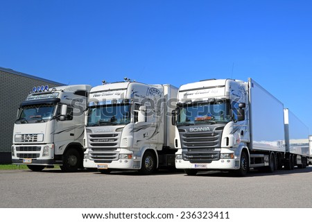 TURKU, FINLAND - SEPTEMBER 13, 2014: Fleet of white Scania R and Volvo FH trucks by a warehouse. According to Statistic Finland, 67 million tonnes of goods were transported by lorries in Q2 of 2014.  - stock photo
