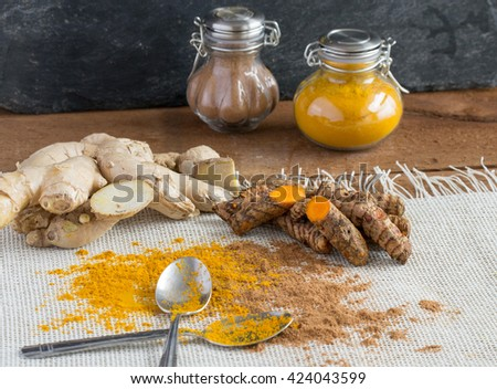 Turmeric and turmeric root with ginger and ground ginger - black slate background, fancy bottles - stock photo