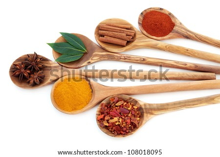 Turmeric, bay leaf herb, chili flakes, star anise, cinnamon sticks and cayenne pepper spice in olive wood spoons over white background. - stock photo