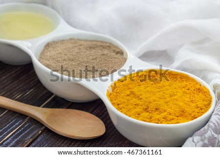 Turmeric, black pepper and olive oil in white ceramic bowl on wooden background. Ingredients for golden paste