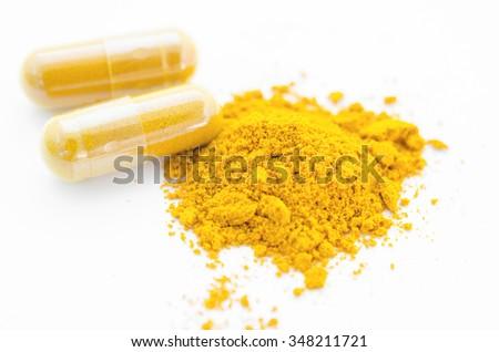 Turmeric herbal powder in capsule on white background. - stock photo