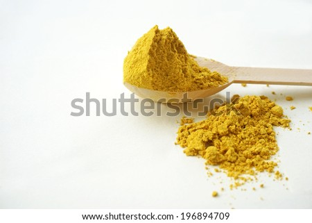 turmeric over the spoon on white background