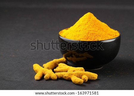 Turmeric powder in  bowl with turmeric sticks - stock photo
