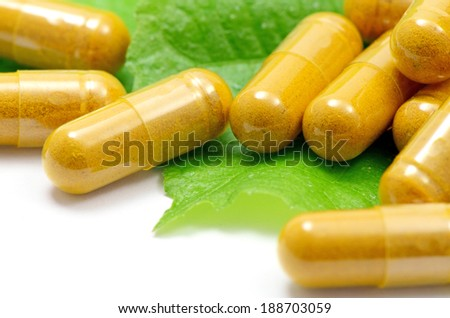 Turmeric Powder in Transparency Hard Gelatin Capsules Contain in Amber Glass Light resistant Bottle Displayed with Green Natural Leaves on White Background.