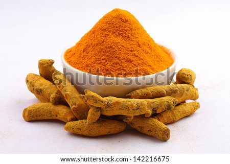 Turmeric powder in white bowl with turmeric sticks isolated onwhite background. - stock photo