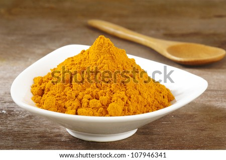 turmeric powder in white dish on wooden background - stock photo