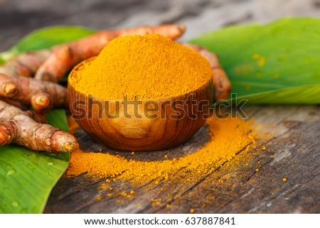 Turmeric powder in wooden bowls on old wooden table