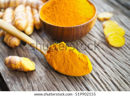 Turmeric powder in wooden spoon on old wooden table. herbal