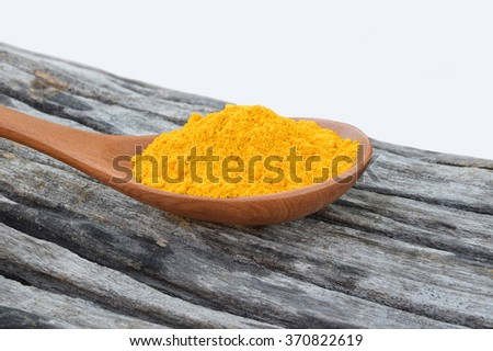 Turmeric powder on the wooden spoon and the old wood texture.Selective focus with shallow depth of field.