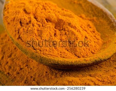 Turmeric powder on  wooden spoon. selective focus - stock photo