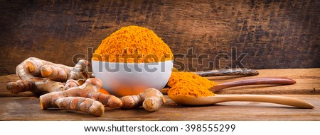 Turmeric roots with turmeric powder on wooden background - stock photo
