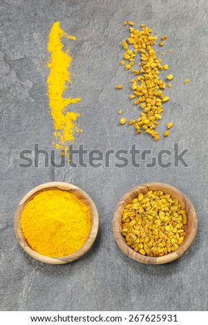 Turmeric. Top angle view of turmeric in olive wood bowls, presented In various forms,  pieces and ground. Macro, selective focus - stock photo