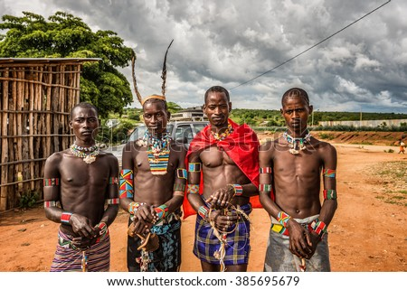TURMI, OMO VALLEY, ETHIOPIA - MAY 5, 2015: Young men from the ethiopian tribes tsamai, Banna and Hamar with traditional jewelry at a popular local market. - stock photo