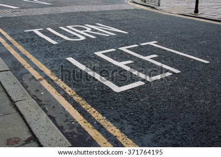 Turn left lettering on pavement in United Kingdom - stock photo