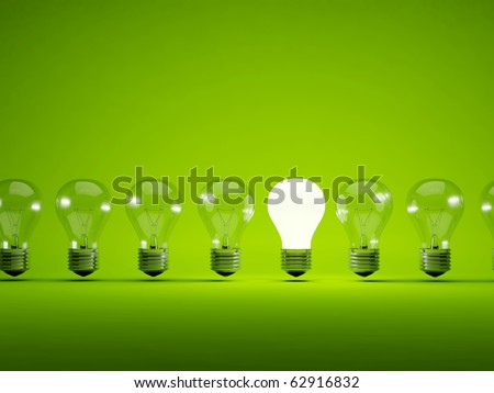 Turn on bulb on green background - stock photo