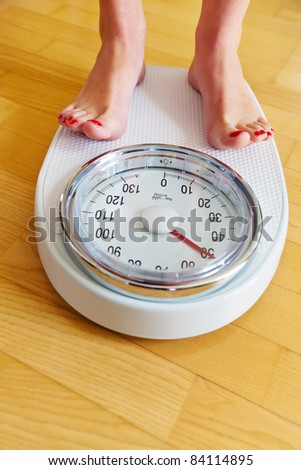 Turn the feet of a woman standing on bathroom scales to - stock photo