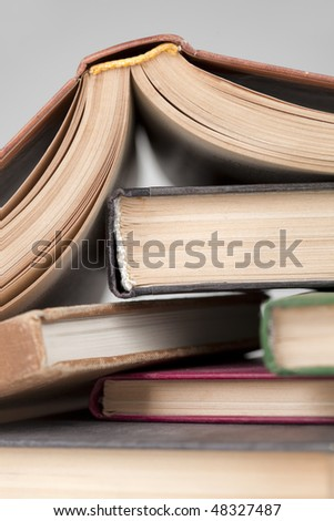Turned down open book on few books in stock - stock photo